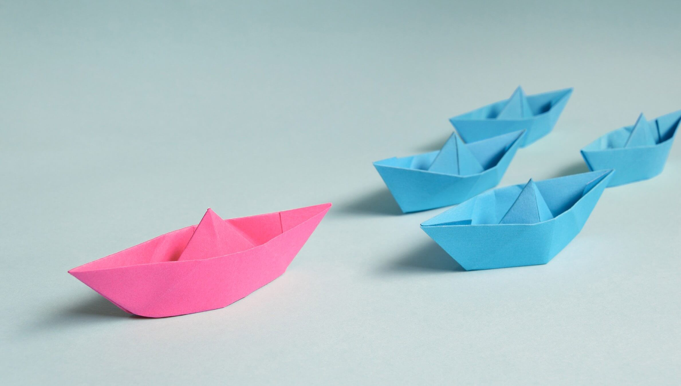 A photo of one pink boat leading four small blue boats.